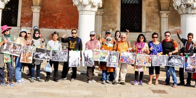 Indonesian tourists hold up photographs of Kolkata in Rome as part of The Sainthood