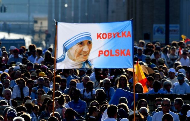 Polish faithful hold a banner reading the name of their city as they arrive to attend the Canonisation...