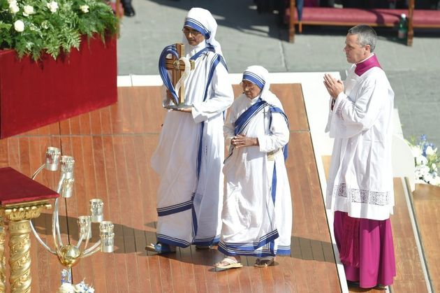 Nuns of the Missionary of Charity carry the mother's relics as a religious man prays during a holy mass...