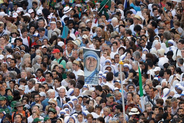 Faithful and pilgrims wait to enter in St. Peter's Square at the Vatican before the canonisation