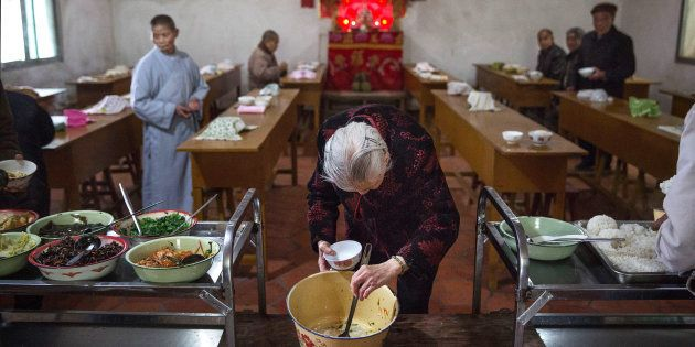 SHA COUNTY, CHINA - MARCH 18: An elderly Chinese resident serves herself food during lunch at the Ji...