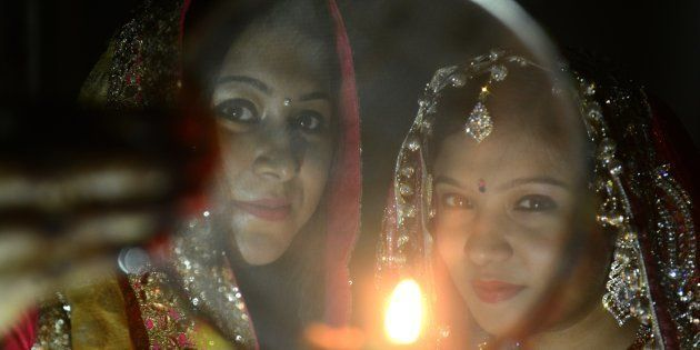 Indian Hindu married women perform a ritual on the occasion of the Hindu festival of Karva Chauth (Husband's...