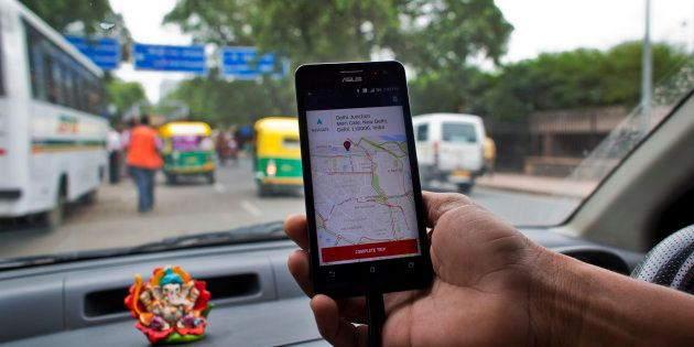 An Indian cab driver displays the city map on a smartphone provided by Uber as he drives in New