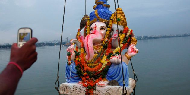 A devotee takes a picture of Hindu god Ganesha as it is lifted to be immersed in the Hussain Sagar Lake...