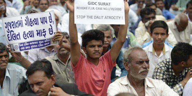 An Indian member of the Dalit caste community holds a placard saying 'In Gujarat, Cow Slaughter is a...