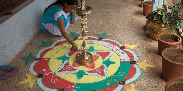Woman making rangoli during Onam Festival, Kerala, India.