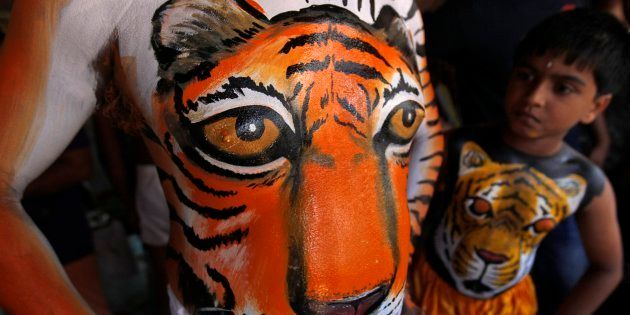A child, his body painted in the likeness of a tiger, looks at the body art of an adult before performing the annual 'Pulikali' or Tiger Dance in Thrissur.