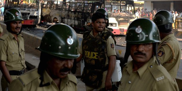 Police personnel stand guard near burnt buses after violence that followed a protest by garment factory...