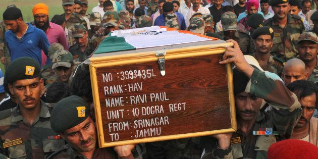 Soldiers carry a coffin containing the body of their fallen colleague Ravi Paul, killed in Sunday's attack...