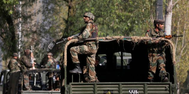Indian soldiers guard outside the army base which was attacked Sunday by suspected militants at Uri,...