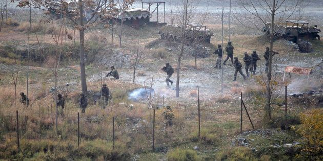Indian army soldiers search for suspected militants as smoke rises from a bunker after a gunbattle in...