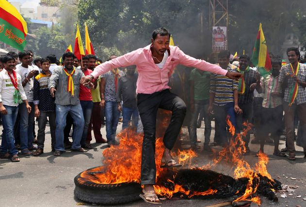 An activist jumps over a burning effigy of Tamil Nadu CM Jayalalitha during a protest against a recent...