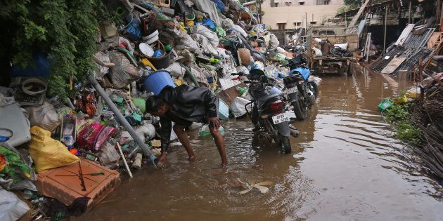 A scrap dealer arranges his collection after rainwater flooded his yard, on the outskirts of
