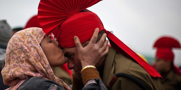 File photo of a Kashmiri Muslim woman kissing her son after his passing out