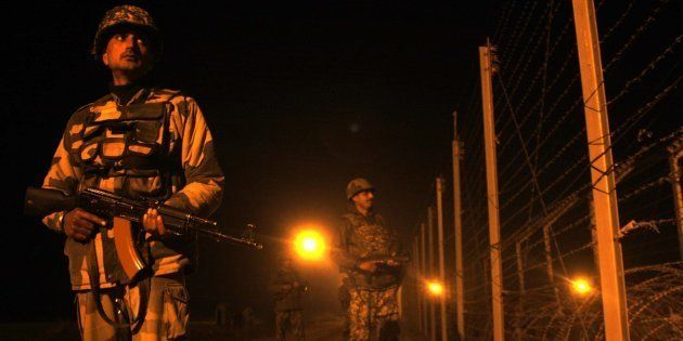 Indian Border Security Force (BSF) soldier stand guard during night patrol near the fenced border with...