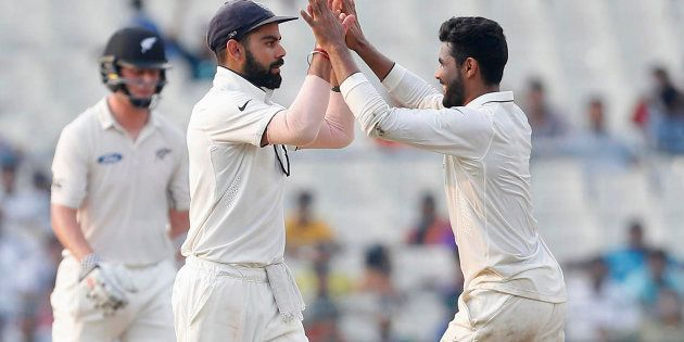 India's Ravindra Jadeja (R) celebrates with his captain Virat Kohli after taking the wicket of New Zealand's...