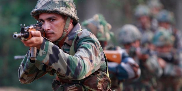 Indian army soldiers take positions during their patrol near the Line of Control in Nowshera sector,...