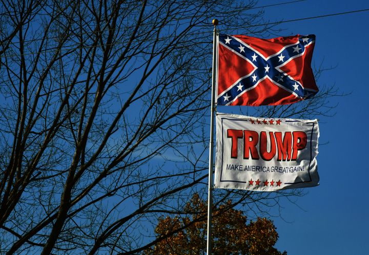 The Confederate Flag and a Trump MAGA flag fly along the Lincoln Highway near a video store in Chester, West Virginia. (Photo