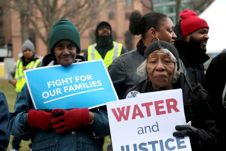 """One of the protesters holds a sign reading """"WATER and JUSTICE,"""" a reference to the ongoing Flint water crisis."""