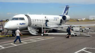 DENVER, CO - September 7, 2016:  Passengers board a SkyWest Airlines Bombardier CRJ-100 passenger plane at Denver International Airport on September 7, 2016. (Photo by Robert Alexander/Getty Images)