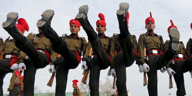 Indian army recruits wearing their ceremonial uniform perform a salute as they pose before their passing...