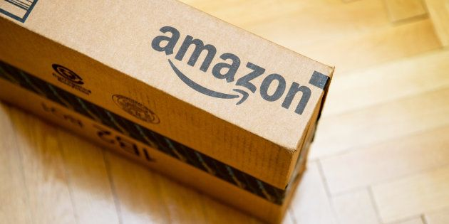 Amazon logotype printed on cardboard box side seen from above on a wooden parwuet