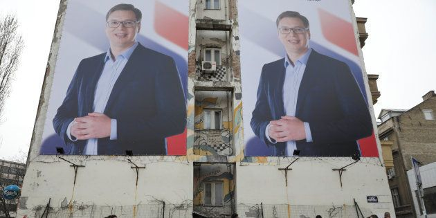 People pass posters of Serbian prime minister Aleksandar Vucic, in Novi Sad, Serbia March 18,