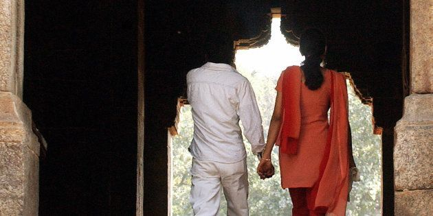 A young Indian couple hold each other's hand as they visit a monument in a park on Valentine's