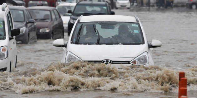 SRINAGAR, INDIA - APRIL 6: Vehicles navigate their way through a waterlogged street after fresh snowfall...
