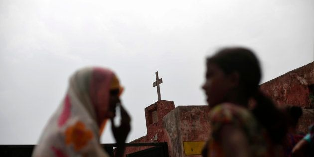 Women speak as they stand outside a church in Uttar