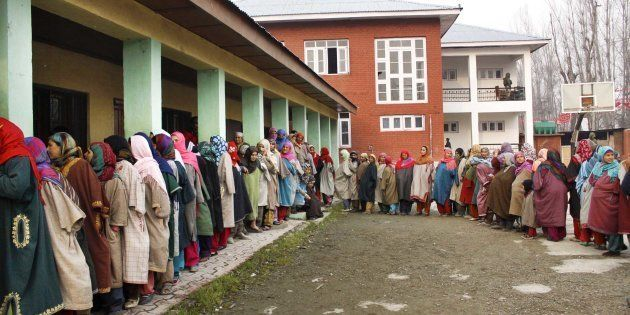 Kashmiri women stand in a queue to cast their