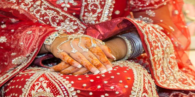 Asian bride rests henna tattoo hands on her wedding