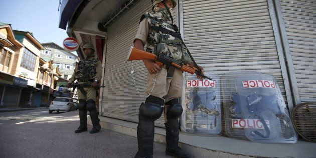Indian Central Reserve Police Force (CRPF) personnel stand guard in front of closed shops during a strike...