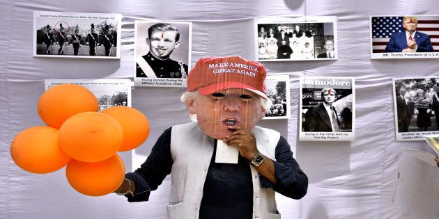 Member of Hindu Sena puts mask of US President Donald Trump as they celebrate his birthday on June 14,...