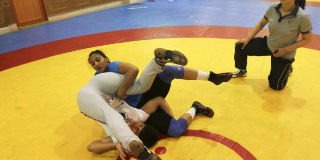 Indian wrestler Geeta Phogat (in blue) practices with a colleague as her coach Monika Choudhary (R) watches...