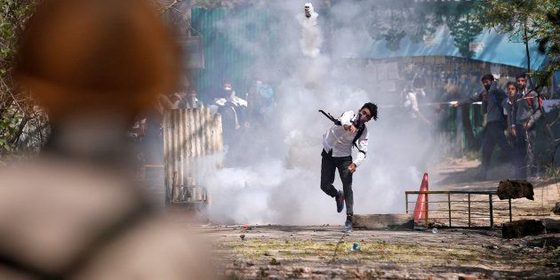 A Kashmiri student throws back a tear-gas canister fired by Indian police during a protest in Srinagar...
