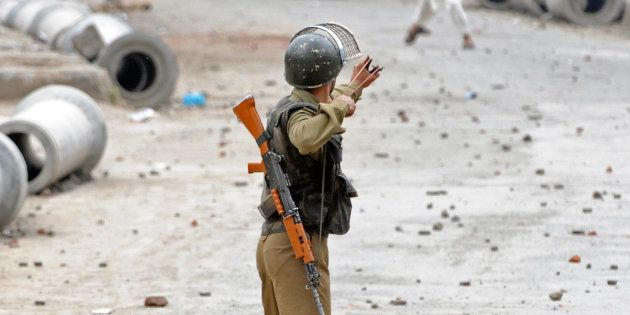 An Indian paramilitary policeman aims his slingshot towards a Kashmiri demonstrator during an anti-election...