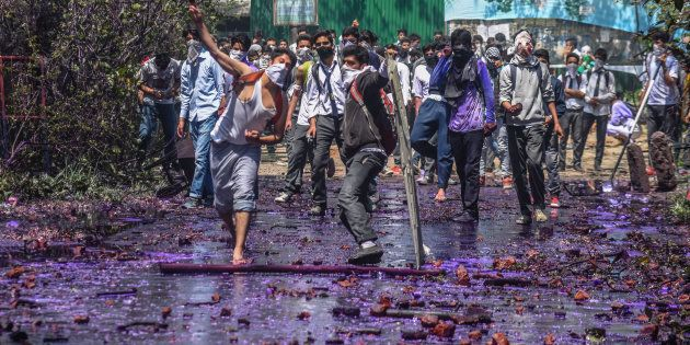 Kashmiri students throw stones at government forces, after they tried to march in the city's main commercial...