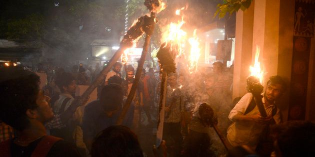 Activists participate in a torch rally against the communal violence in