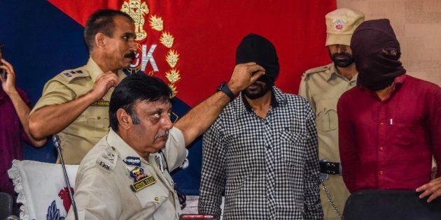 Muneer Ahmed Khan, Inspector General of police Kashmir, shows Sandeep Kumar, a Hindu non-local, militant...