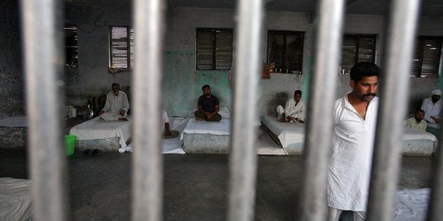 File photo of inmates resting behind bars in a barrack at Kotbhalwal central jail in Jammu May 18,