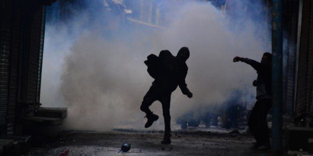 File photo of a boy pelting stones at police personnel amidst heavy tear gas