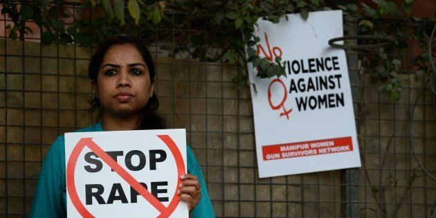 An Indian social activist holds a placard during a protest against a rape at Hauz Khas village in New
