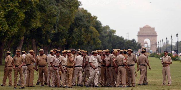 Police officers gather for a briefing near the India Gate in New