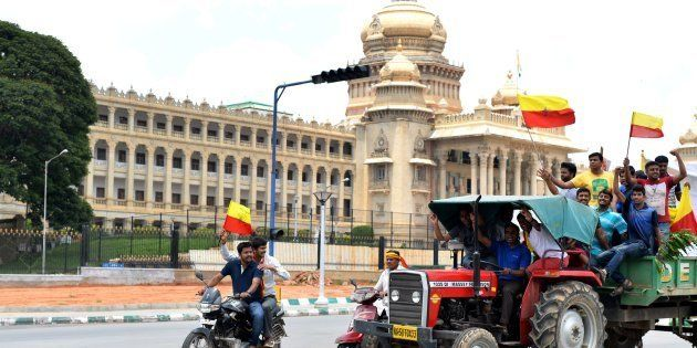 Pro-Karnataka activists wave the Karnataka flag at a rally during a statewide strike in Bangalore on...