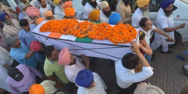 Baljit Kaur (3R) and her son Amritbir Singh (2R) carry the coffin of her husband Indian Central Reserve...
