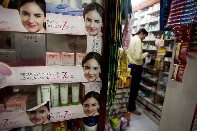 A pharmacy manager works in his shop where beauty and fairness products are displayed in Mumbai, India,...