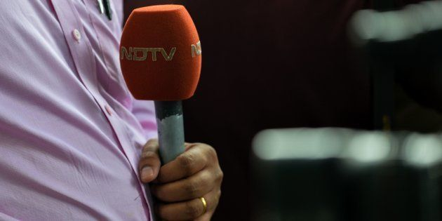 A news reporter with the Indian news channel NDTV holds a microphone in New Delhi on November 4,