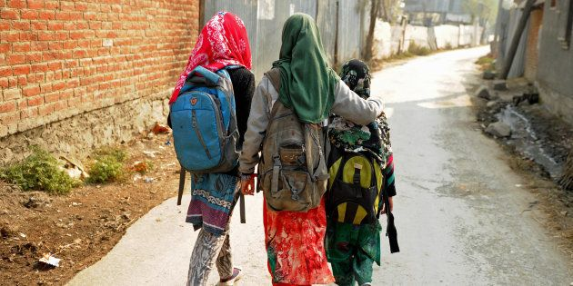 Kashmiri students walk home after attending an ad-hoc learning center on the outskirts of