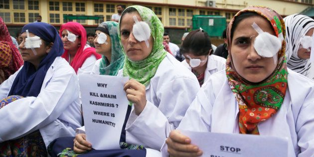 Kashmiri doctors and medical workers wear bandages on their eyes as a mark of protest against the use...